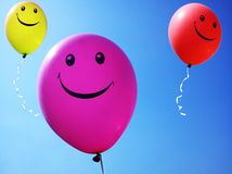 Smiling baloons flying up with blue background